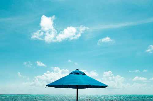 close up photo of blue parasol near body of water under blue sky